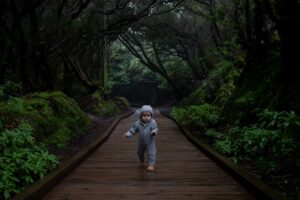 focused toddler running on middle of footpath