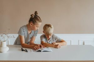 little girl helping her brother with homework
