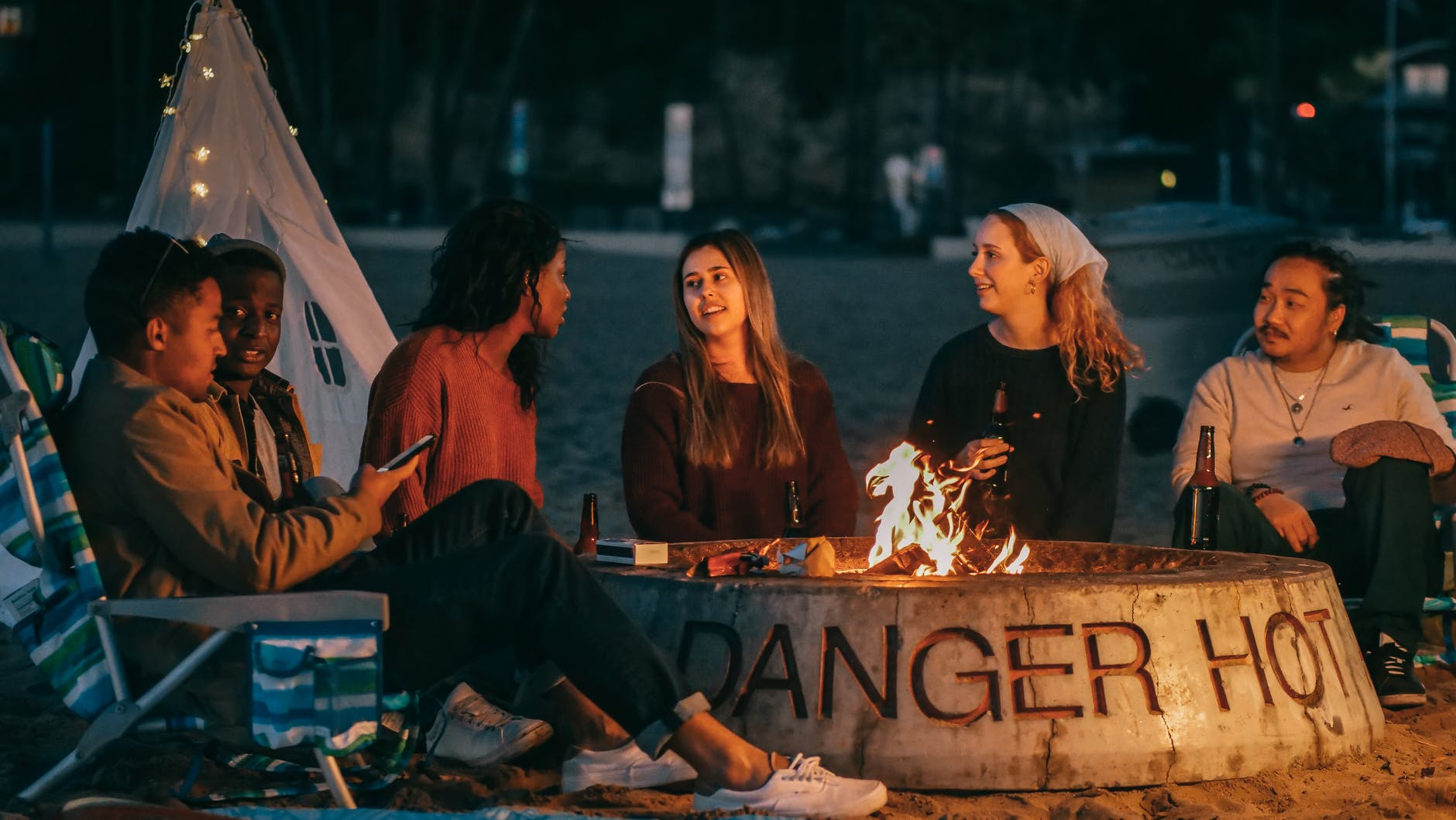 group of friends sitting in front of fire pit